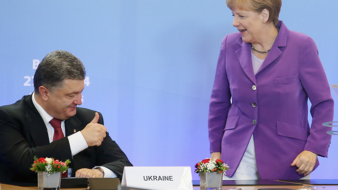 Ukraine's President Petro Poroshenko gives a thumbs up to Germany's Chancellor Angela Merkel (R) during a signing ceremony of cooperation agreement at the EU Council in Brussels June 27, 2014 (Reuters / Olivier Hoslet)