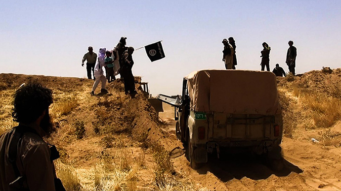 A file image made available by the jihadist Twitter account Al-Baraka news on June 9, 2014 allegedly shows Islamic State of Iraq and the Levant (ISIL) militants waving the trademark Jihadits flag as vehicles drive on a newly cut road through the Syrian-Iraqi border between the Iraqi Nineveh province and the Syrian town of Al-Hasakah (AFP Photo)