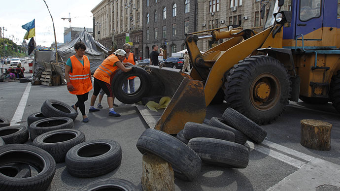 Municipal workers remove tyres as they dismantle barricades set up during the protests that toppled Moscow-backed president Viktor Yanukovich in central Kiev July 1, 2014. (Reuters / Valentyn Ogirenko)