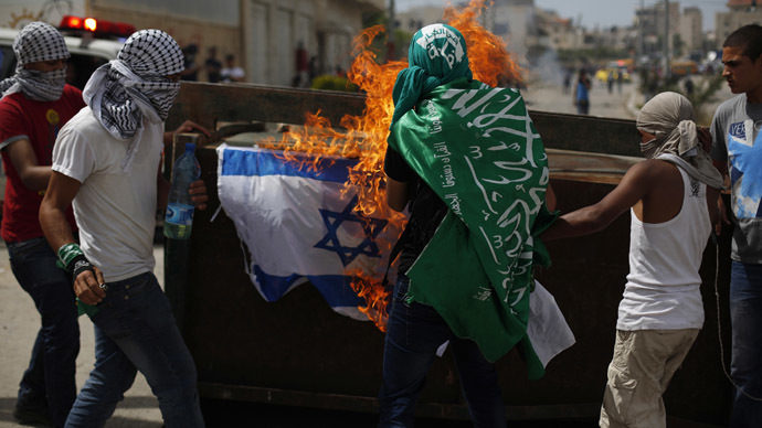 Palestinian protesters burn an Israeli flag during clashes with Israeli troops near Israel's Ofer Prison, near the West Bank city of Ramallah May 16, 2014. (Reuters/Mohamad Torokman)