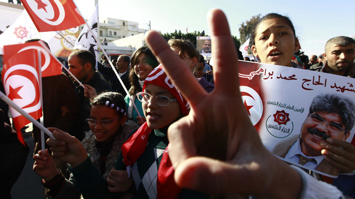 People wave Tunisian flags as another holds a picture of slain opposition leader Mohamed Brahmi during a rally in Sidi Bouzid December 17, 2013, to mark the third anniversary of the Tunisian revolution. (Reuters)
