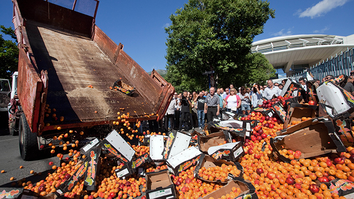 People stand by unexportable fruits discharged in front of the fence of the local prefecture building on July 9, 2014 in Bastia, Corsica, as part of a protest gathering hundreds of local business owners and elected to protest against French government incapacity to put an end to a six weeks long conflict with employees of the SNCM ferry compagny (AFP Photo)