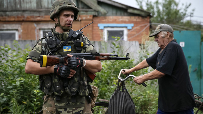 "A local resident pushes a bicycle past a member of Ukrainian police special task force ""Kiev-1"" patrolling in the eastern Ukrainian village of Semenovka, near Sloviansk, July 14, 2014. (Reuters/Gleb Garanich)"