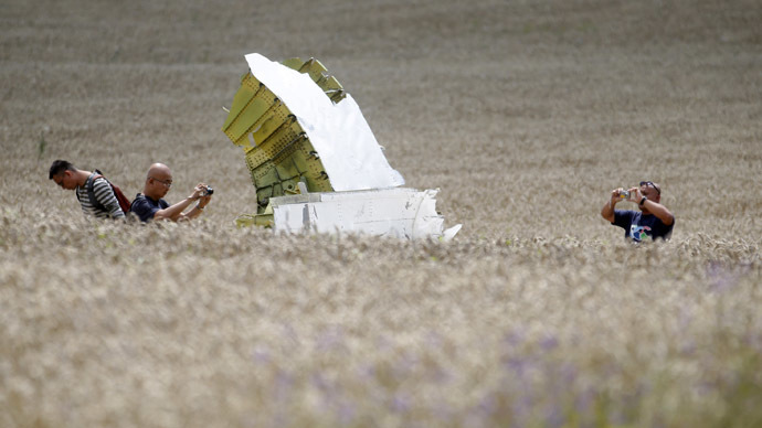 Malaysian air crash investigators take photos of the crash site of Malaysia Airlines Flight MH17, near the village of Hrabove (Grabovo), Donetsk region July 22, 2014. (Reuters/Maxim Zmeyev)