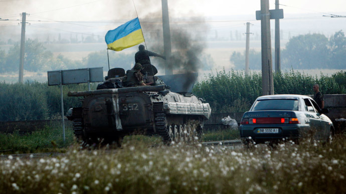 Ukrainian servicemen drive a military armoured vehicle along a road in Donetsk region August 6, 2014.(Reuters / Valentyn Ogirenko)