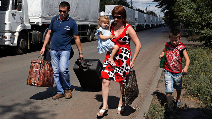 People walk past trucks of a Russian convoy carrying humanitarian aid for Ukraine near a Russia-Ukraine border crossing point in Rostov Region, August 21, 2014 (Reuters / Alexander Demianchuk)