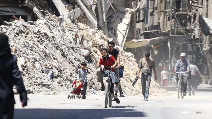 Boys ride a bicycle past other civilians near damaged buildings in the Damascus suburb of Harasta August 24, 2014. (Reuters/Badra Mamet)