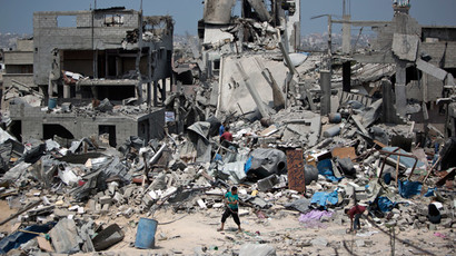 Palestinian men walk on the rubble of their destroyed houses in the Tufah neighbourhood in eastern Gaza City on August 31, 2014.(AFP Photo / Mahmud Hams )