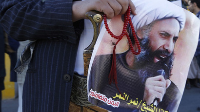 A Shi'ite protester carries a poster of Sheikh Nimr al-Nimr during a demonstration outside the Saudi embassy in Sanaa October 18, 2014. (Reuters/Khaled Abdullah)