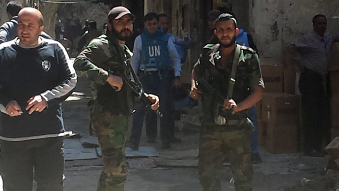 "Palestinian ""volunteer forces"" stand guard while NGOs tend to Yarmouk camp residents receiving food aid, medical assistance and evacuation."