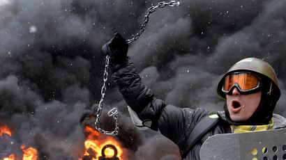 In a picture taken on January 22, 2014 a demonstrator holds up a chain and a riot police shield as protestors clash with police in the center of Kiev. (AFP Photo / Sergei Supinsky)