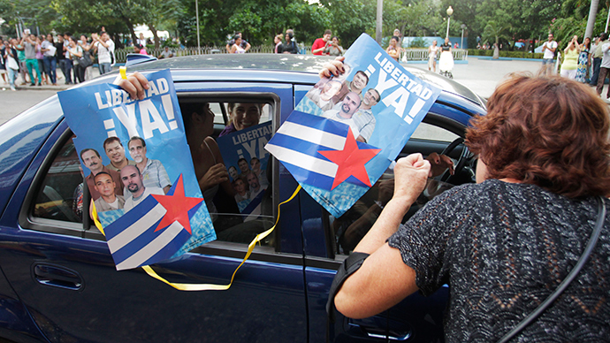 "A woman celebrates with people riding in a car and holding posters of the ""Cuban Five"" in Havana December 17, 2014 (Reuters / Stringer)"