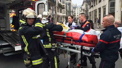 "Firefighters carry an injured man on a stretcher in front of the offices of the French satirical newspaper Charlie Hebdo in Paris on January 7, 2015, after armed gunmen stormed the offices leaving at least one dead according to a police source and ""six seriously injured"" police officers according to City Hall. (AFP Photo/Philippe Dupeyrat)"