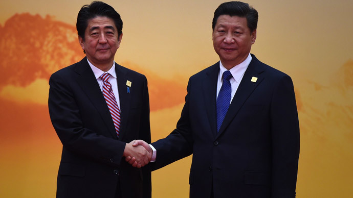 Japan's Prime Minister Shinzo Abe (L) shakes hands with China's President Xi Jinping as he arrives for the Asia-Pacific Economic Cooperation (APEC) leaders meeting at Yanqi Lake, north of Beijing on November 11, 2014. (AFP Photo / Greg Baker)