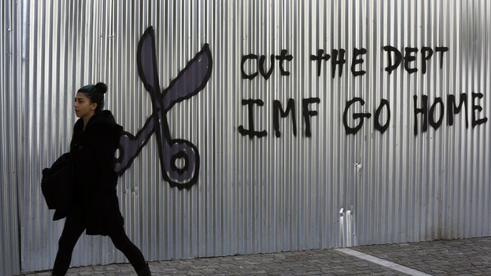 A woman walks by anti-International Monetary Fund graffiti in central Athens, February 2, 2015. (Reuters/Yannis Behrakis)
