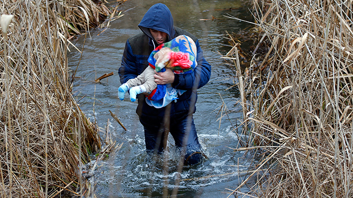 A Kosovo man carries his baby as he crosses illegally the Hungarian-Serbian border near the village of Asotthalom February 6, 2015 (Reuters / Laszlo Balogh)