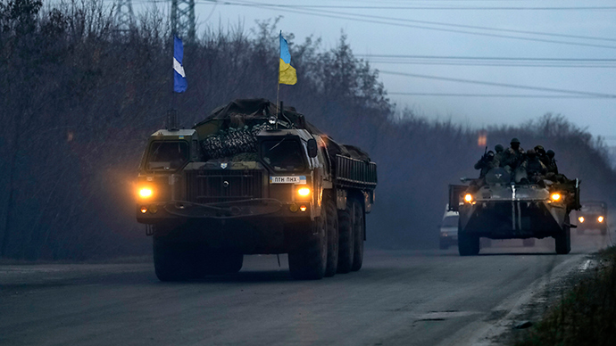 Members of the Ukrainian armed forces ride on an armoured personnel carrier as they guard a convoy of multiple rocket launcher systems belonging to the Ukrainian armed forces near Kramatorsk, eastern Ukraine March 6, 2015 (Reuters / Gleb Garanich)