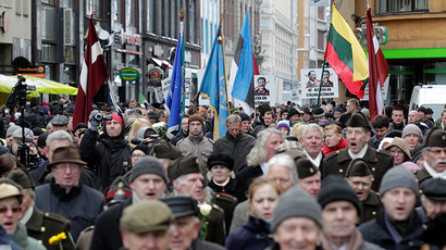People take part in the annual procession commemorating the Latvian Waffen-SS (Schutzstaffel) unit, also known as the Legionnaires, in Riga March 16, 2014 (Reuters / Ints Kalnins)