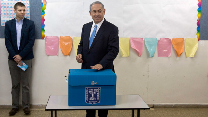Israel's Prime Minister Benjamin Netanyahu casts his ballot for the parliamentary election as his son Yair stands behind him at a polling station in Jerusalem March 17, 2015.  (Reuters / Sebastian Scheiner / Pool)