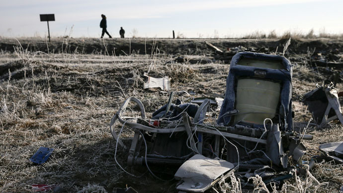 Men walk past the wreckage of MH17, a Malaysia Airlines Boeing 777 plane, at the site of the plane crash near the village of Hrabove (Grabovo) in Donetsk region, December 15, 2014. (Reuters/Maxim Shemetov)