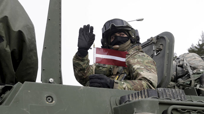 "A soldier of the U.S. Army 2nd Cavalry Regiment deployed in Estonia, as a part of the U.S. military's Operation Atlantic Resolve, holds a Latvian flag and waves as he arrives during the ""Dragoon Ride"" exercise in Liepupe March 22, 2015. (Reuters/Ints Kalnins)"