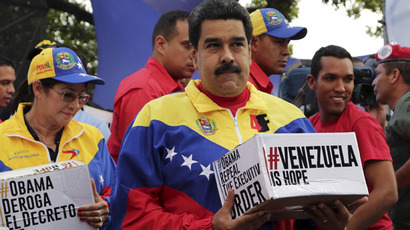 Venezuela's President Nicolas Maduro carries a box containing signatures to ask U.S. President Barack Obama to lift sanctions against a group of Venezuelan army members during a rally outside Miraflores Palace in Caracas April 9, 2015. (Reuters/Marco Bello)