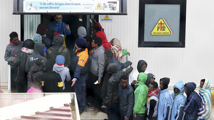 Migrants stand in front of the infirmary at the immigration centre on the southern Italian island of Lampedusa February 19, 2015. (Reuters/Alessandro Bianchi)