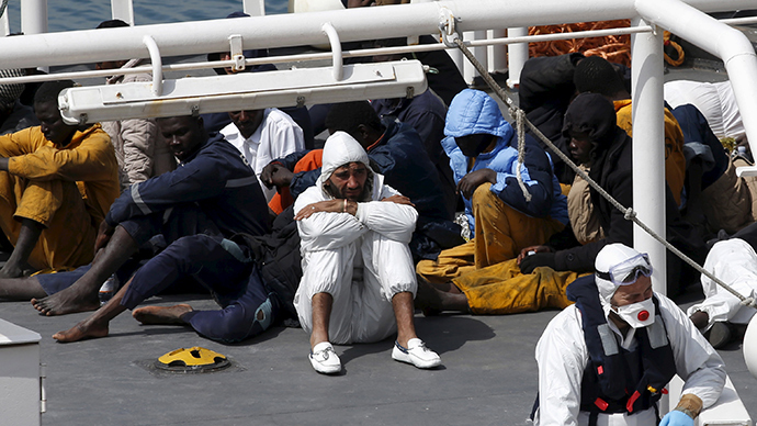 Mohammed Ali Malek (C, in white), one of two survivors of Saturday's migrant boat disaster, later arrested on suspicion of people trafficking, is seen watching bodies of dead migrants being disembarked from the Italian coastguard ship Bruno Gregoretti in Senglea in Valletta's Grand Harbour April 20, 2015 (Reuters / Darrin Zammit Lupi)