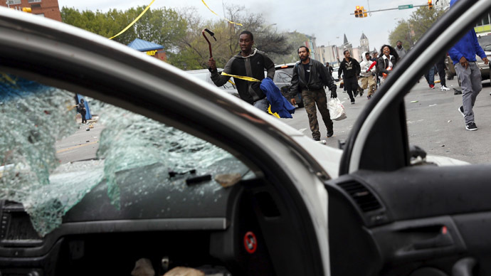 Demonstrators run by a damaged Baltimore police vehicle during clashes in Baltimore, Maryland April 27, 2015. (Reuters/Shannon Stapleton)