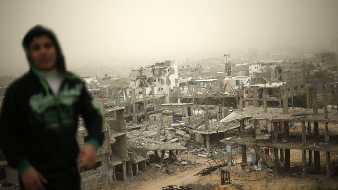 A Palestinian stands in front of ruined houses, which witnesses said were destroyed by Israeli shelling during a 50-day war last summer, on a stormy day in the east of Gaza City February 10, 2015. (Reuters/Mohammed Salem)