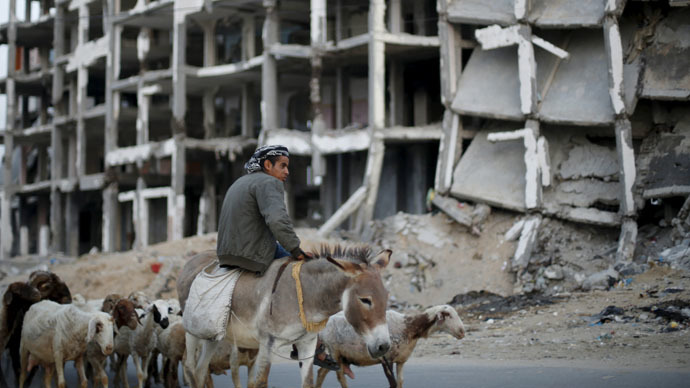 A Palestinian shepherd rides a donkey as he herds livestock past residential buildings, that witnesses said were heavily damaged by Israeli shelling during a 50-day war last summer, in Beit Lahiya town in the northern Gaza Strip May 25, 2015. (Reuters/Suhaib Salem )
