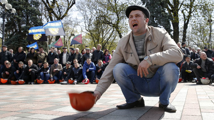 A miner bangs his helmet on the ground during a rally, to demand the payment of their salaries and reforms in the coal industry, in front of the parliament building in Kiev April 23, 2015. (Reuters/Valentyn Ogirenko)