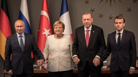 Angela Merkel, Vladimir Poutine, Recep Tayyip Erdogan et Emmanuel Macron se tiennent la main lors du sommet d'Istanbul, le 27 octobre 2018.