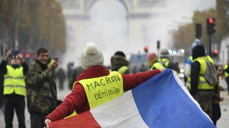 Une manifestante vêtue d'un gilet jaune arbore un drapeau tricolore sur les Champs-Elysées, le 24 novembre 2018.